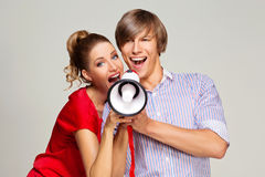 Happy couple screaming in megaphone Stock Images