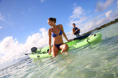 Happy couple in the se with canoe. Beautiful women with bikini posing sitted on canoe stock images