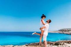 Happy couple by the sea. Man and woman having fun on the sea. Honeymoon lovers. Man and woman on the island. Couple in love on royalty free stock image