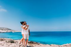 Happy couple by the sea. Man and woman hugging on the beach. Honeymoon lovers. Man and woman on the island. Couple in love on stock image