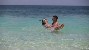 Happy couple in sea water. The young man holds the girl on hands, they stand in sea water on a tropical beach.The man turns the girl on water.Love and the stock video