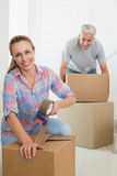 Happy couple sealing cardboard moving boxes Stock Photos