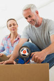 Happy couple sealing cardboard moving boxes. In their old home Royalty Free Stock Image