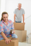 Happy couple sealing cardboard moving boxes. In their old home Stock Photos