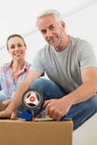 Happy couple sealing cardboard moving boxes. In their old home Royalty Free Stock Images