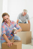 Happy couple sealing cardboard moving boxes. In their old home Stock Image