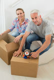 Happy couple sealing cardboard moving boxes. In their old home Stock Images