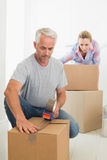 Happy couple sealing cardboard moving boxes. In their old home Royalty Free Stock Photography