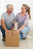 Happy couple sealing cardboard moving boxes. In their old home Stock Photo