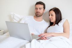 Happy couple searching for consumer advice in internet Stock Photography