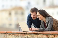 Happy couple searching online content on a laptop. In a balcony on vacation stock photo