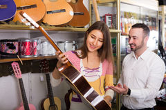Happy couple selecting acoustic guitar in shop Royalty Free Stock Images