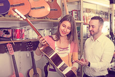 Happy couple selecting acoustic guitar in shop Stock Images