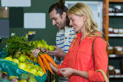 Happy couple selecting fruits and carrots in organic section Royalty Free Stock Photo