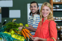 Happy couple selecting fruits and carrots in organic section Stock Image