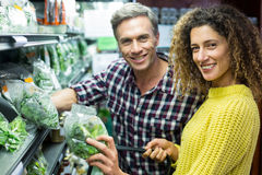 Happy couple selecting vegetables in organic section Stock Photo