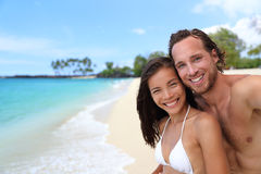 Happy couple selfie on exotic beach vacation. Beautiful interracial young adults smiling taking a self-portrait photo with mobile phone on tropical travel royalty free stock photos