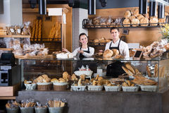 Happy couple selling pastry and loaves. Happy couple selling fresh pastry and loaves in bread section royalty free stock photography