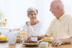 Happy couple of seniors. Looking at each other while eating breakfast and drinking tea royalty free stock images