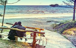 Happy couple of seniors are resting at sandy beach of the Baltic Sea Royalty Free Stock Images