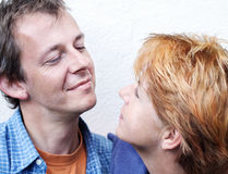 Happy couple series. Middle-age couple looking face to face,blue clothes on white background, outdoor,man is happy to see her stock photography