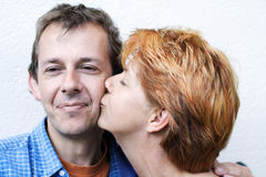 Happy couple series. Middle-age couple is happy,woman in profile is kissing the man,outdoor on white background,copper color hair of the woman stock photos