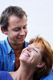 Happy couple series. Middle-age couple with blue clothes on white background,outdoor, woman is laying on his shoulder and laughing, man is looking at her royalty free stock images