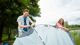 Happy couple setting up tent outdoors Royalty Free Stock Image