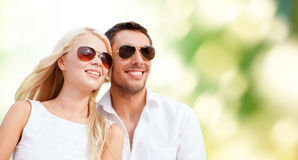 Happy couple in shades over green background. Summer holidays, people, ecology and dating concept - happy couple in shades over green background stock photography
