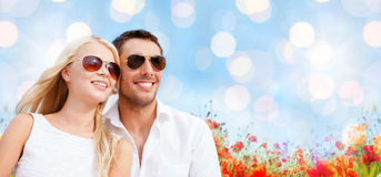 Happy couple in shades over poppy field background Royalty Free Stock Images