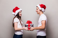 Happy couple share christmas gift. On grey background stock images