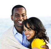 Happy couple sharing blanket. Young romantic sharing a blanket by the ocean Stock Image