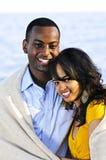 Happy couple sharing blanket Stock Image