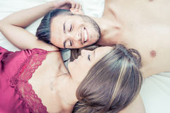 Happy couple sharing moments in bed Royalty Free Stock Photography