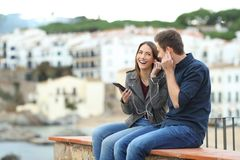 Happy couple sharing music on a ledge. Happy couple sharing online music from a smart phone sitting on a ledge on vacation in a coast town stock images