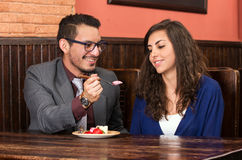 Happy couple sharing strawberry dessert in Stock Photo