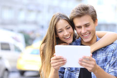 Happy couple sharing a tablet in the street Stock Photo