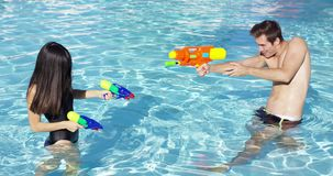 Happy couple shooting off water guns in pool. Happy young male and female couple shooting off colorful plastic water guns at each other in swimming pool stock video