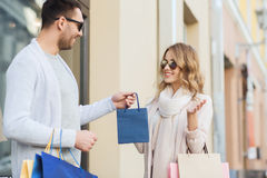 Happy couple with shopping bags in city Stock Photos