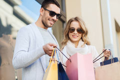 Happy couple with shopping bags on city street. Sale, consumerism and people concept - happy couple looking into shopping bag at shop window on city street Royalty Free Stock Images