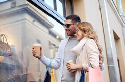 Happy couple with shopping bags and coffee in city Stock Photos