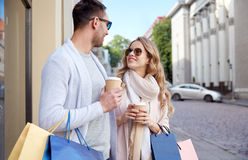 Happy couple with shopping bags and coffee in city Stock Image