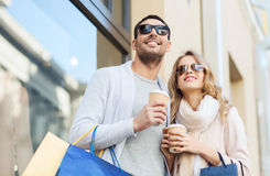 Happy couple with shopping bags and coffee in city. Sale, consumerism and people concept - happy couple with shopping bags and coffee paper cups at shop window Stock Photography