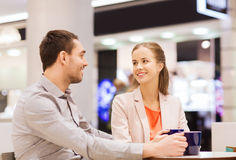 Happy couple with shopping bags drinking coffee Stock Images