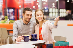 Happy couple with shopping bags drinking coffee Stock Image