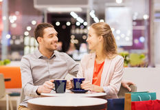 Happy couple with shopping bags drinking coffee Royalty Free Stock Photo