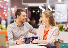 Happy couple with shopping bags drinking coffee Royalty Free Stock Photos