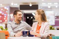 Happy couple with shopping bags drinking coffee. Sale, shopping, consumerism, leisure and people concept - happy couple with shopping bags drinking coffee in Royalty Free Stock Image