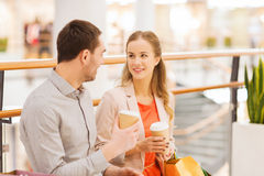 Happy couple with shopping bags drinking coffee. Sale, shopping, consumerism, leisure and people concept - happy couple with shopping bags drinking coffee from Royalty Free Stock Photo