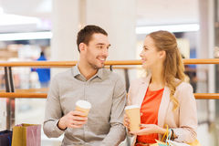 Happy couple with shopping bags drinking coffee. Sale, shopping, consumerism, leisure and people concept - happy couple with shopping bags drinking coffee from Royalty Free Stock Image